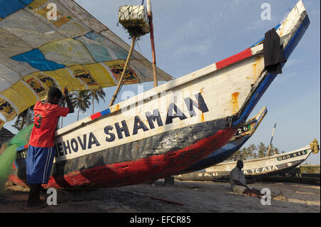 A fishermen stows his nets in the boat after fishing of the coast of Accra, Ghana, West Africa. - Stock Photo