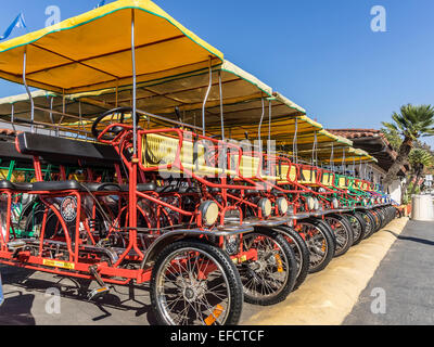 A row of multicolor, 4-person rental surreys lined up by the beach in Santa Barbara, California for use by tourists. - Stock Photo