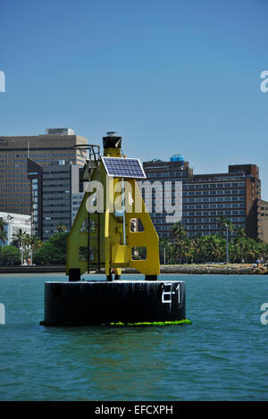 Solar powered yellow and black channel marker buoy in Durban harbour, KwaZulu-Natal, South Africa - Stock Photo