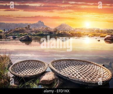 Round shape boats on Tungabhadra river at sunset sky in Hampi, Karnataka, India - Stock Photo