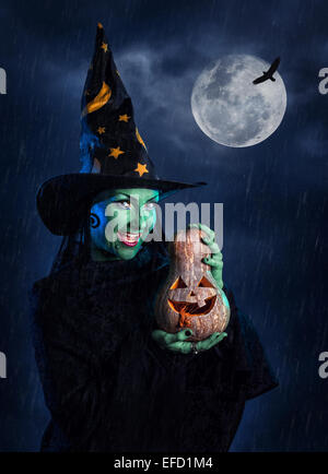 Witch with green skin holding carved Halloween pumpkin at moon and dark sky with rain - Stock Photo