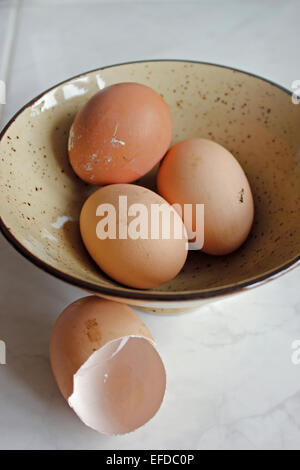 Three free-range eggs in a bowl plus one empty egg shell - Stock Photo