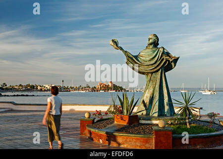 Woman walking by sculpture of person holding a shell and bay, Malecon (seaside promenade), La Paz, Baja California - Stock Photo