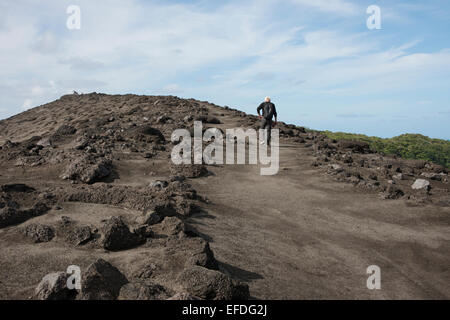 Melanesia, Vanuatu, Tanna Island. Mt. Yasur volcano, crater trail around volcano. Tourists hiking on the volcano - Stock Photo