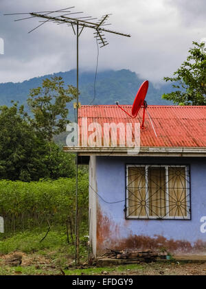 Telecommunication priorities of large aerial and satellite dish on the roof of a little house in Costa Rica - Stock Photo