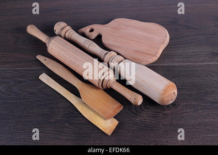 Wooden kitchen accessories on a brown background. - Stock Photo