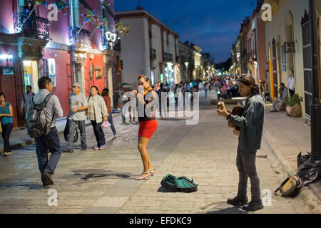 Oaxaca, Mexico - A woman and man play the violin and guitar for tips on a pedestrian street. - Stock Photo