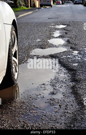 Wet potholes in road, Stanwell Moor, Surrey, England, United Kingdom - Stock Photo