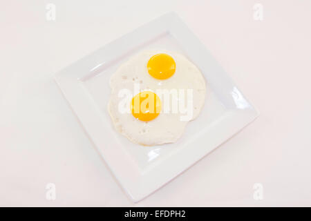 Two fried eggs on a white plate - Stock Photo