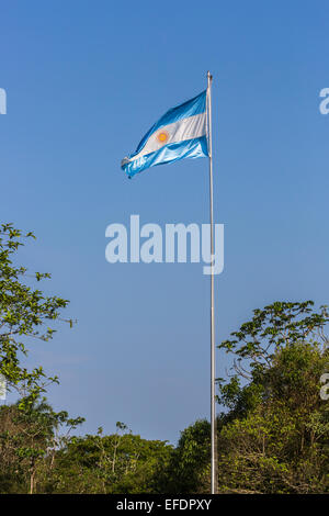 Blue and white Argentinian flag flying from a flagpole against a blue sky on a sunny day in Argentina - Stock Photo