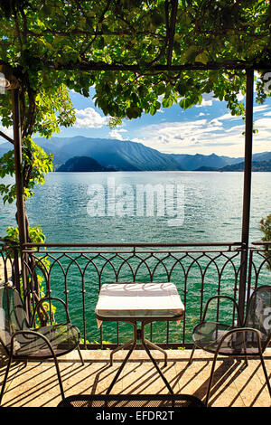 View of a Small Table Under a Trellis with a Lake View, Varenna, Lake Como, Lombardy, Italy - Stock Photo