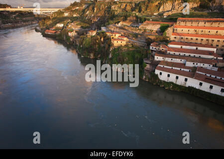 Sunset at Vila Nova de Gaia and Porto in Portugal. Wine cellars and warehouses on a steep shore of the Douro river. - Stock Photo