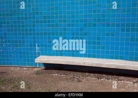Wall with blue tiles and concrete bench near the sea. - Stock Photo