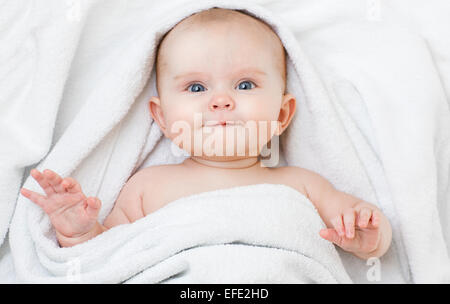 Cute funny smiling baby lying on back in bathing towel - Stock Photo