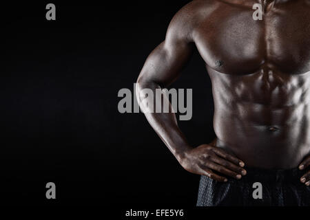 Close-up of shirtless african man with hands on hip while standing against black background. Cropped image of torso - Stock Photo
