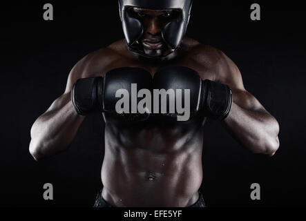 Portrait of young african male boxer preparing for competition against black background. Muscular male model wearing - Stock Photo