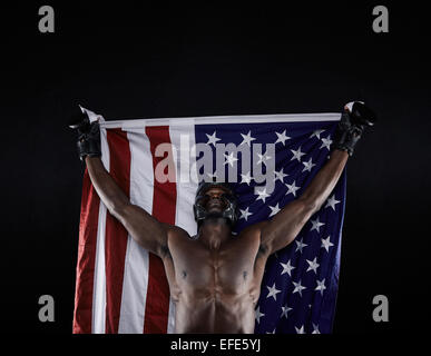 Young boxer carrying american flag raised in victory on black background. American boxing champion celebrating success. - Stock Photo