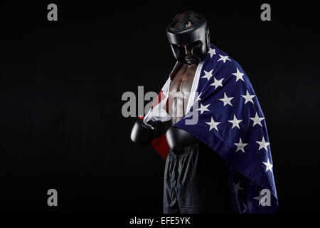 Portrait of young male boxer with American flag on black background. African man in boxing gear looking down. - Stock Photo