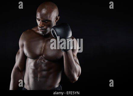 Portrait of determined young boxer thinking of his moves on black background. Male boxer practicing boxing with - Stock Photo