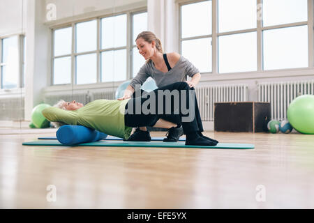 Female trainer instructing senior woman going exercise on a foam roller. Elder woman doing pilates workout with - Stock Photo