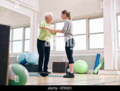 Female trainer helping senior woman in a gym exercising with a bosu balance training platform. Elder woman being - Stock Photo