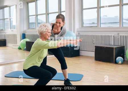 Elderly woman doing exercise with her personal trainer at gym. Gym instructor assisting senior woman in her workout. - Stock Photo
