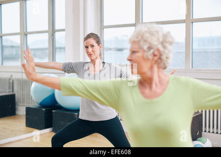 Two women doing stretching and aerobics workout at gym. Female trainer in background with senior woman in front - Stock Photo