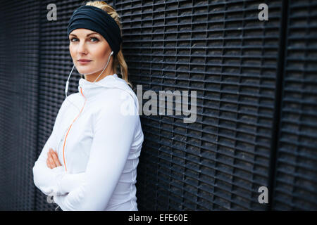 Portrait of sporty young woman wearing earphones standing leaning a wall looking confidently at camera. Fit female - Stock Photo