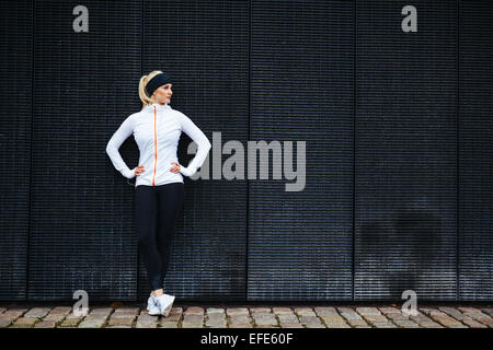 Determined woman resting after jogging in the city. Full length shot of sporty young woman relaxing after running - Stock Photo