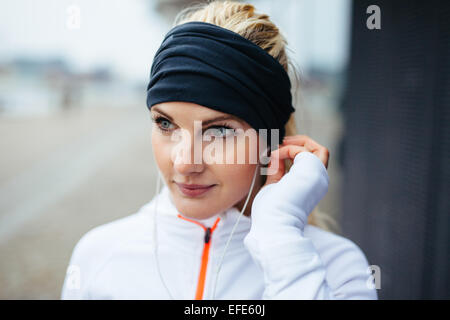 Close-up portrait of beautiful sportswoman wearing headband and listening to music on earphones. Fitness female - Stock Photo