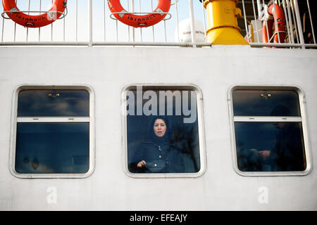 A woman peers out at the view on a bosphorous ferry is pictured as part of a photo essay on winter breaks in Istanbul, - Stock Photo
