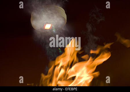 A smoke alarm with emergency light activated by smoke, with flame approaching - Stock Photo
