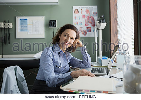 Portrait of doctor at laptop in doctors office - Stock Photo