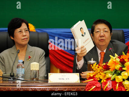 Phnom Penh, Cambodia. 2nd Feb, 2015. Cambodian Deputy Prime Minister and Cabinet Minister Sok An (R) shows the book - Stock Photo