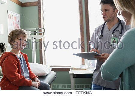 Smiling boy talking to mother and male nurse - Stock Photo