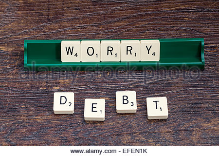 Worry and Debt spelled out with scrabble letters - Stock Photo