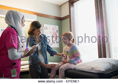 Nurse wearing hijab talking to girl - Stock Photo