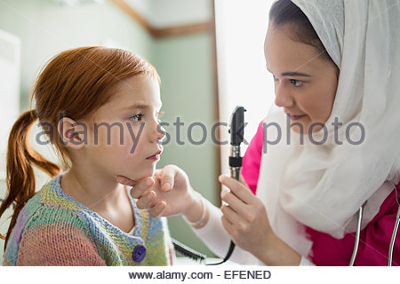 Nurse wearing hijab checking vision of girl - Stock Photo