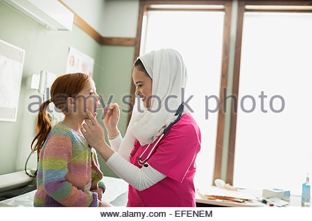 Nurse wearing hijab using tongue depressor on girl - Stock Photo