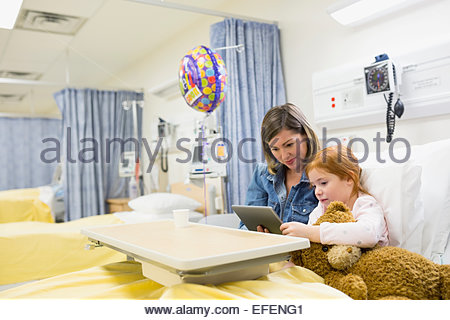 Mother and daughter using digital tablet in hospital - Stock Photo