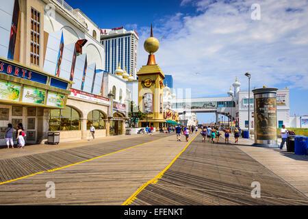 Tourists walk on the boardwalk in Atlantic City. - Stock Photo