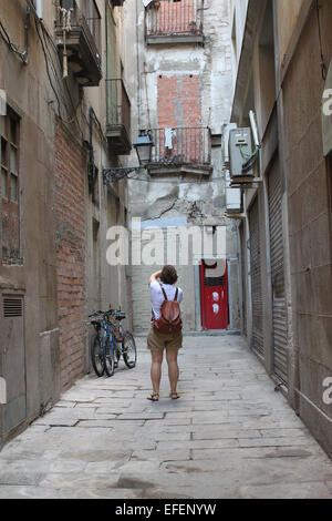 Woman taking photos in narrow back street with bricked up doors and windows in the Gothic Quarter of Barcelona, - Stock Photo