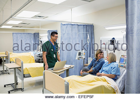 Male nurse checking on patient in hospital - Stock Photo