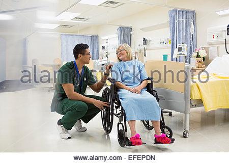 Male nurse talking to woman in hospital wheelchair - Stock Photo