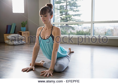 Woman practicing yoga in pigeon pose - Stock Photo