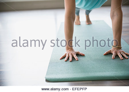 Woman practicing yoga on mat in plank pose - Stock Photo