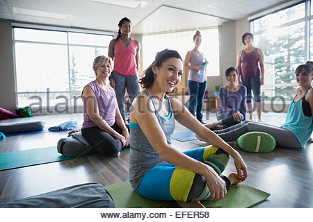 Smiling women in restorative yoga class - Stock Photo