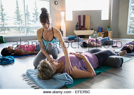 Instructor adjusting students shoulders in restorative yoga class - Stock Photo