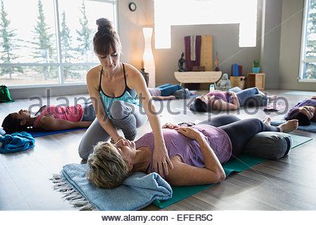 Instructor adjusting students shoulders in restorative yoga class - Stock Photo