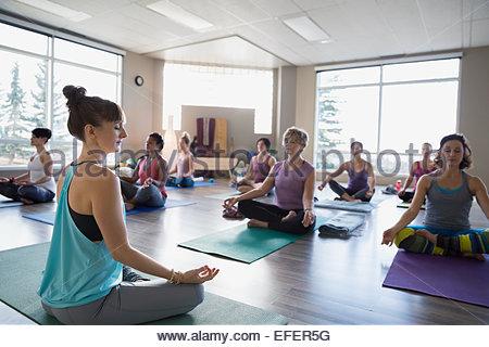 Women in mudra lotus position in yoga class - Stock Photo